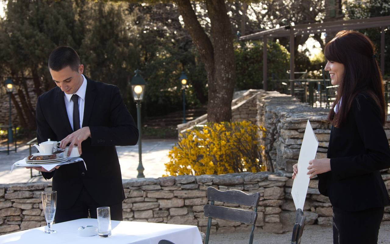 Terrace of the restaurant with waiter, michelin restaurant in Gordes, in Provence, Hotel Les Bories